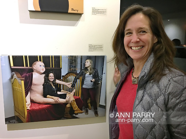 "Huntington, New York, USA. March 5, 2017. LORI HOROWITZ next to 2014 photo of herself, at Opening Reception for ""Her Story Through Art"" Invitational Art Show, celebrating Women's History Month, at Huntington Arts Council, Main Street Gallery. Artists Tara Leale Porter, Irene Vitale, Anahi DeCanio, Ann Parry, Show March 2 - 25, 2017. (Ann Parry/Ann Parry, ann-parry.com)"
