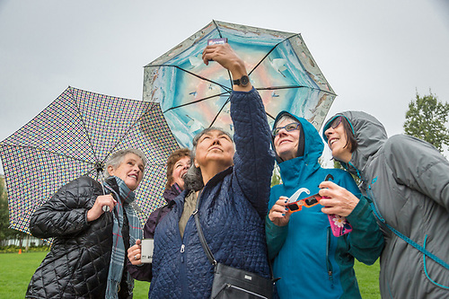 "8:38 AM, Anchorage, Alaska.  Barrow resident Dorcas Stein shows her friends the ""virtual image"" of the solar eclipse with the aid of skyview app on her iPhone in front of the Anchorage Museum. (Clark James Mishler)"