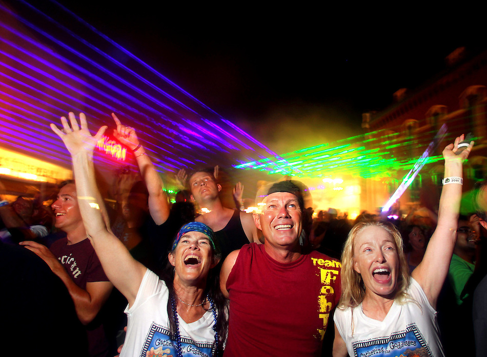 Gina Pfarr of Sioux Falls, S.D., left, Mark Giffen of Springfield, Mo., and Tisa Overman of Milwaukee, Wis., revel in a laser light show with other fun-seekers in downtown Grinnell on July 28 during the fifth night of  RAGBRAI XXXIX. (Christopher Gannon/The Register)