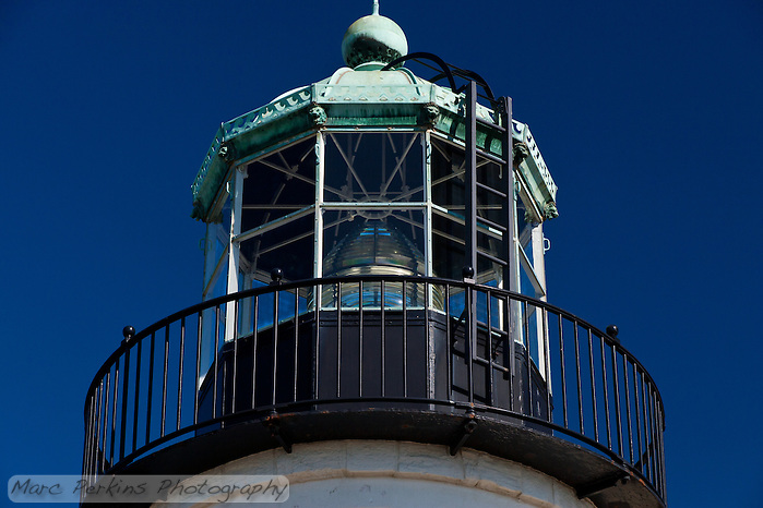 A close-up view of the lantern room and its attached black-painted balcony seen from beneath.  The lantern room appears to be towering above the viewer, and the details on the lantern room's green (copper?) roof are easily visible.  For instance, the room can be seen to have lion or gargoyle figureheads at each of the room's 10 corners, and above each window is a cut-out pattern in the roof's edging of what look to be waves heading towards each other with the cutouts themselves appearing to be horns.   A black ladder climbs to the top of the copper roof, reading the large dome on top.  The white, black, and green building contrast beautifully with the dark blue sky. The lighthouse is in Cabrillo National Monument near San Diego, CA.  I have another version of this same view that is less cropped, if you want. (Marc C. Perkins)