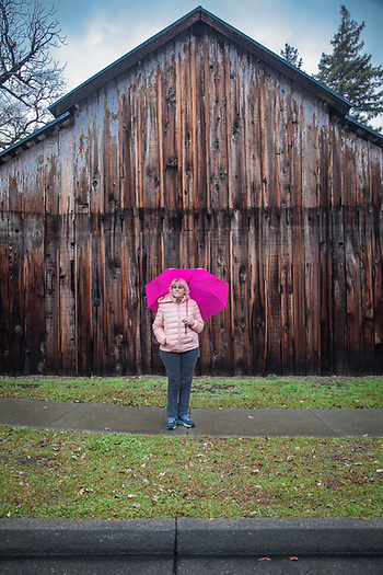 "Retired micro biologist, Judy Miles, on a rainy day at the end of Cedar Street in Calistoga  ""I retired last year after 24 years with Beringer...I love being retired...I gotta go...you're keeping me from a date with a cup of coffee."" (Clark James Mishler)"