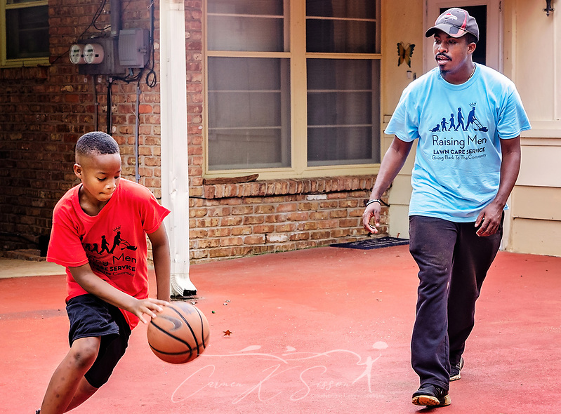 Quay Knight dribbles a basketball as Rodney Smith Jr. offers suggestions on his technique, Aug. 1, 2018, in Huntsville, Ala. Quay, along with his brother, Lamar, is among more than 250 youth cutting grass as part of Raising Men Lawn Care Service, a non-profit organization Smith founded which provides free lawn care for the elderly, disabled, veterans, and single mothers. (Photo by Carmen K. Sisson) (Carmen K. Sisson/Cloudybright)
