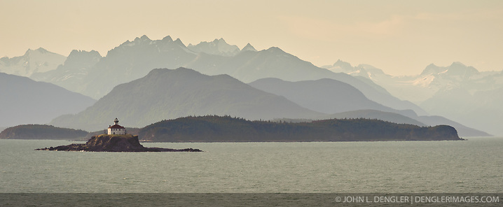 The mountains of the Chilkat Range serve as a backdrop for evening sunlight on the Eldred Rock Lighthouse, located on the Lynn Canal in southeast Alaska. Construction of the lighthouse was finished in 1906 after shipwrecks occurred in the area during the 1898 Klondike gold rush. The light was automated by the U.S. Coast Guard in 1973 with the original fourth-order Fresnel lens moved to the Sheldon Museum in Haines. (John L. Dengler)