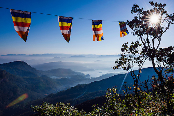 Adam's Peak (Sri Pada), sunstar photo of a misty mountain view with Buddhist flags, Central Highlands of Sri Lanka, Asia. This is a photo of a misty mountain view and Buddhist flags on the climb up Adam's Peak (Sri Pada) in the Central Highlands of Sri Lanka, Asia.