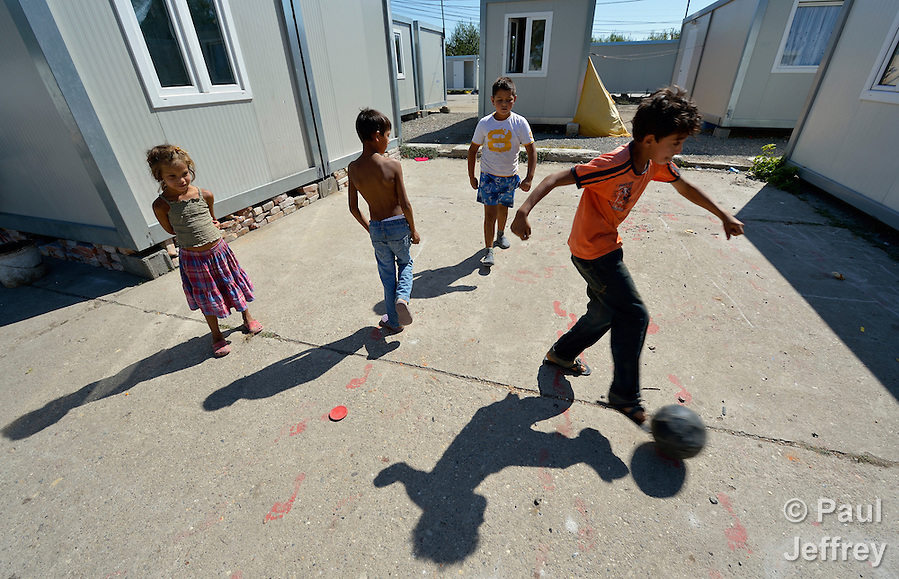 Roma children play football amid shipping containers that have been converted into houses in Makis, a village outside of Belgrade, Serbia. These Roma families were evicted from an urban squatter settlement in 2012 to make way for construction of new apartments and office buildings. The shipping containers they now call home, which were provided at no cost by local authorities, are far from the city center. (Paul Jeffrey)