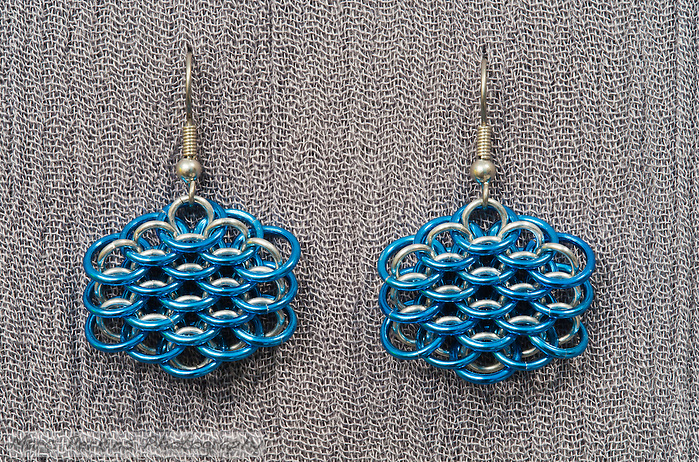 "A pair of chainmail earrings made from blue anodized 18 gauge aluminum rings  and 19 gauge 5/32"" bright aluminum rings woven in a dragonscale pattern.  Made by Michelle. (Marc C. Perkins)"