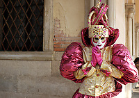 Man dressed in traditional mask and costume for Venice Carnival standing at Doge's Palace, Piazza San Marco, Venice, Veneto, Italy (Brad Mitchell Photography)