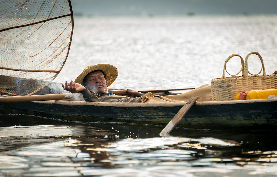 INLE LAKE, MYANMAR - CIRCA DECEMBER 2013: Fisherman taking a rest and smoking in his boat in Inle Lake, Myanmar (Daniel Korzeniewski)