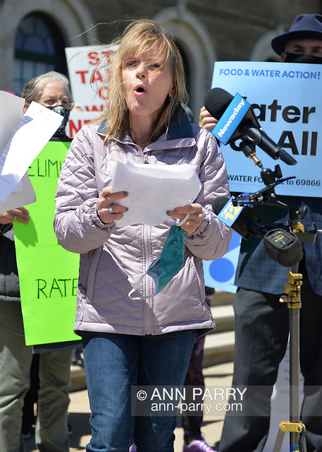 """""""Mineola, NY, USA. April 26, 2021. AGATHA NADEL, Director of North Shore Concerned Citizens (NSCC) speaks at rally, and behind her at right is ERIC WELTMAN, Senior Organizer for Food & Water Watch and Food & Water Action. Faced with a 26% rate increase from New York American Water going into effect May 1, 2021, activists and residents who are NYAW customers rally to urge NYS Assembly to push through legislation, before then, corresponding with NYS Senate Bill S989A to establish a Nassau County Water Authority. (© 2021 Ann Parry/AnnParry.com)"""