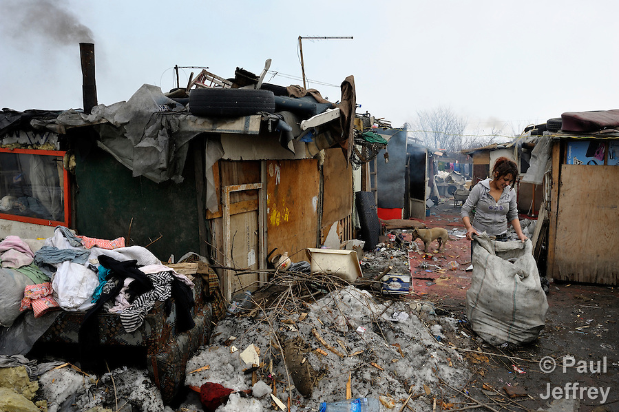 Skurta Hodici, 17, cleans up around her home in the wake of a severe winter storm in February 2012. She lived in an illegal Roma settlement in Belgrade, Serbia. The families that lived here, most of whom survive from recycling cardboard and other materials, were forcibly evicted in April 2012. Many including Hodici were moved into metal shipping containers on the edge of Belgrade. (Paul Jeffrey)