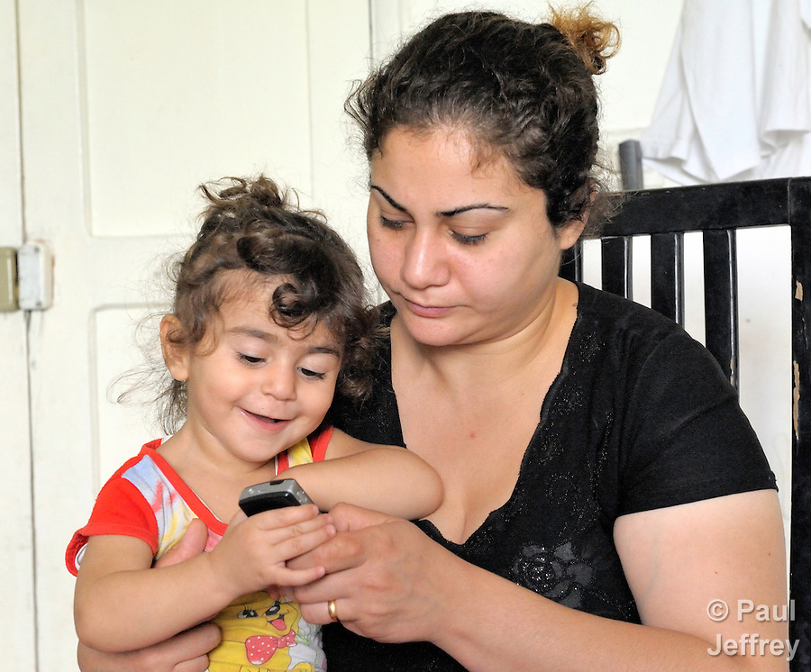 Farah Faris, who is 20 months old, looks at a photo of her dead father on a cell phone belonging to her mother, Rana Ramzi. The girl's father was killed February 29, 2008, in Mosul, Iraq, while working as a driver and assistant to the Chaldean archbishop of Mosul, Archbishop Faraj Rahho, who was later found dead. Rana Ramzi and her three children fled Iraq in May and live as refugees in Lebanon. They have received assistance from the Caritas Lebanon Migrant Center. The family is hoping to resettle in coming months in the United States.