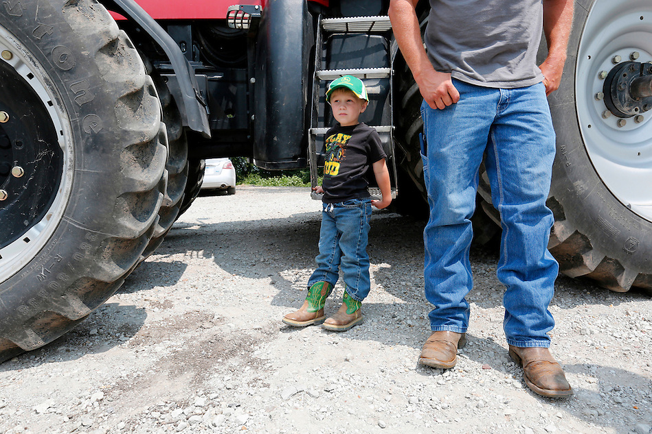 Jayden Dammann, 3, waits for a tractor ride while his father, Justin, visits with others on the family farm in rural Page county on July 19, 2014.  Justin says he feels confident about the management of the family farm one day passing on to Jayden. (Christopher Gannon/The Register)
