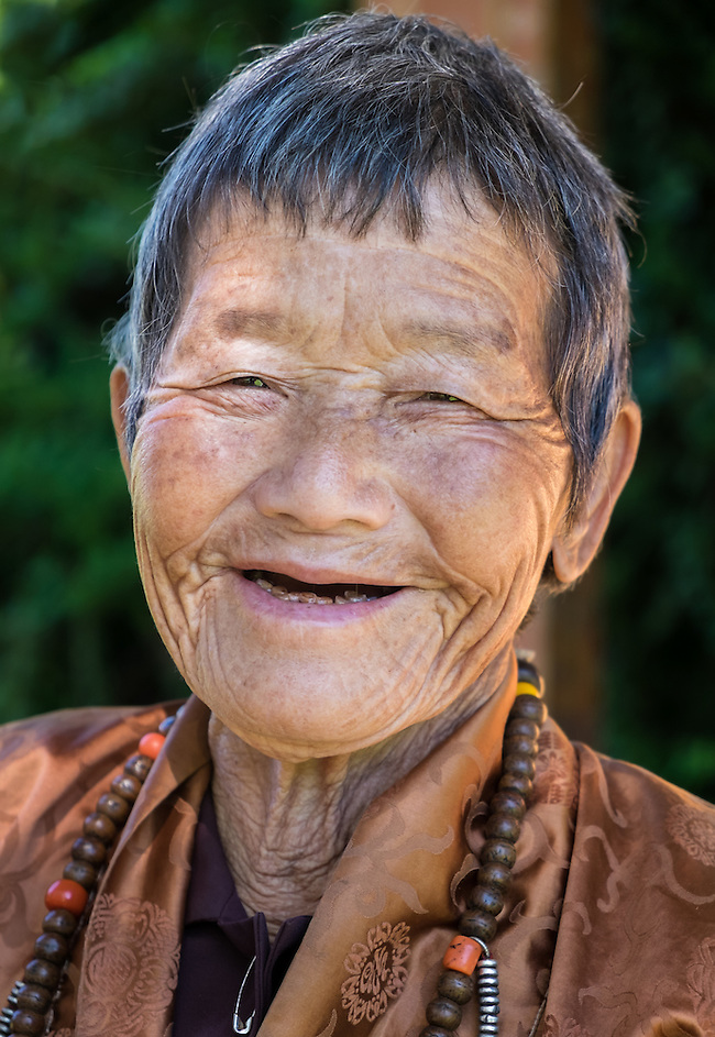 THIMPHU, BHUTAN - CIRCA OCTOBER 2014: Old Bhutanese woman smiling close to the Memorial Chorten in Thimphu (Daniel Korzeniewski)