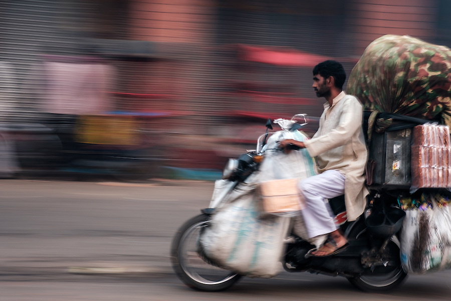 NEW DELHI, INDIA - CIRCA OCTOBER 2016: Man in motorbike in the streets of Delhi carrying goods. (Daniel Korzeniewski)