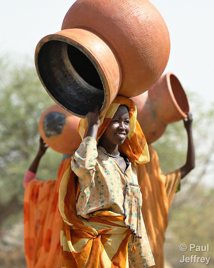 Displaced women in Zalingei, in Sudan's war-torn Darfur region, carry pots they have made to the market to sell.
