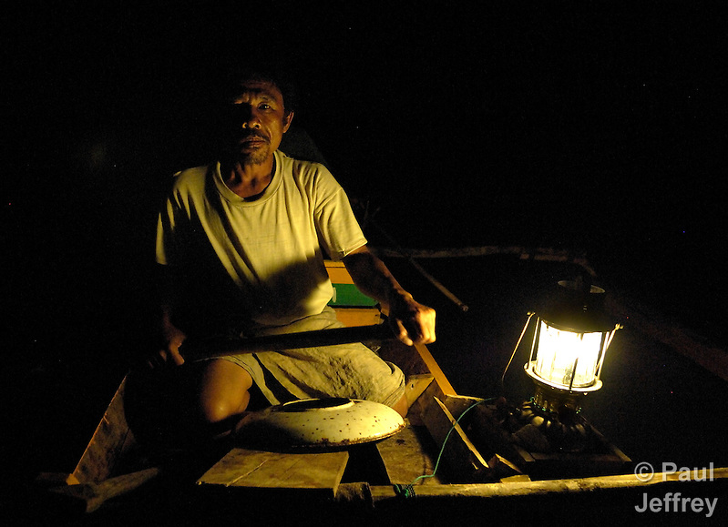 In this photo from 2007, Nurul Huda, a fisherman in the village of Olora on the Indonesian island of Nias, paddles at night to his fishing grounds in a boat provided by Church World Service. CWS and other members of the ACT Alliance helped families devastated by the 2004 tsunami and 2005 earthquake on Nias to rebuild their homes and their livelihoods. (Paul Jeffrey)