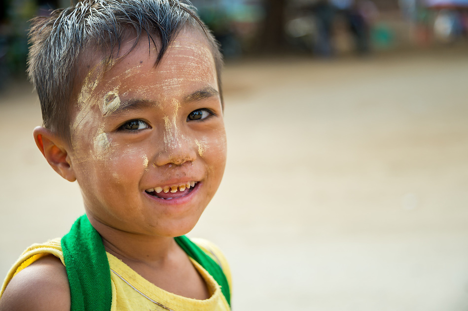 MANDALAY, MYANMAR - CIRCA DECEMBER 2013: Happy Burmese kid smiling and looking at camera playing in the streets of Min Kun in Myanmar (Daniel Korzeniewski)