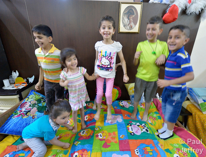 Iraqi children bounce on a bed in the basement of Sacred Heart Catholic church in Amman, Jordan, where 60 Iraqi Christian refugees are living. The Lutheran World Federation, a member of the ACT Alliance, has helped the church feed the refugees and remodel the basement into partitioned areas to provide some privacy for the ten refugee families. Parental consent obtained. (Paul Jeffrey)