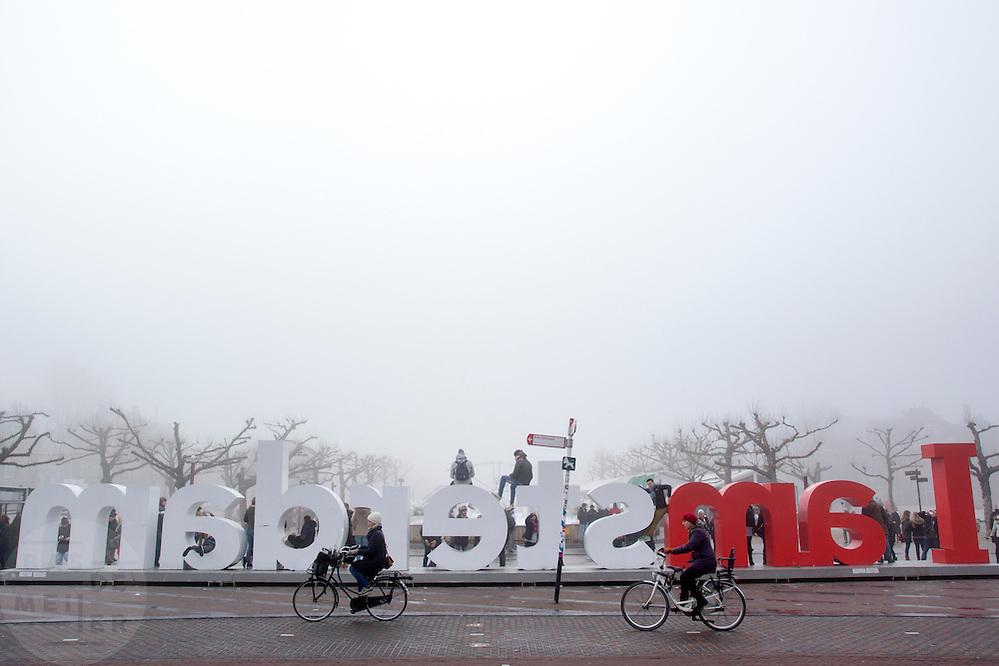In Amsterdam fietsen twee vrouwen langs de tekst I Amsterdam op het Museumplein in de mist.