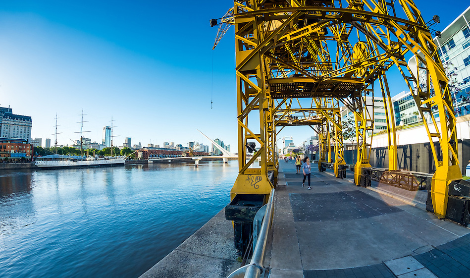 BUENOS AIRES - CIRCA NOVEMBER 2012: View of boardwalk and cranes with La Mujer Bridge in background in the neighborhood of Puerto Madero, circa November 2012. This is a popular tourist destination with over 2.5 million yearly visitors . (Daniel Korzeniewski)