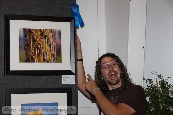 A picture of me with my winning entry at the 2011 Orange County Fair.  The first place blue ribbon is so pretty!  My photograph was in the amateur color print of plants category.  Many thanks to Nafis, who kindly took this picture of me. (Marc C. Perkins)