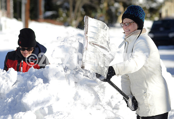 Tara Grunde-McLaughlin (right) of Newtown, Pennsylvania shovels snow rom the sidewalk while cleaning up after Winter Storm Jonas Sunday January 24, 2016 in Newtown, Pennsylvania. (Photo by William Thomas Cain) (William Thomas Cain/Cain Images)