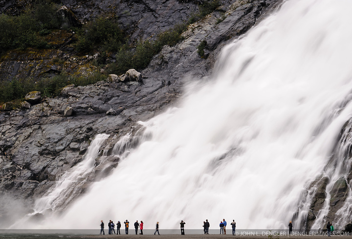 Hikers to Nugget Falls located next to the Mendenhall Glacier near Juneau, Alaska are dwarfed by the 377 foot waterfall. Each year, 465,000 curise ship passengers visit the Mendenhall Glacier. (John L. Dengler)