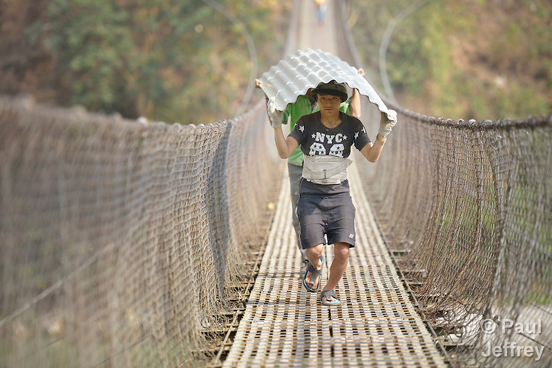 Rebuilding supplies are carried by hand across a suspension bridge into Adamtar, an indigenous village in Nepal's Dhading District where Dan Church Aid, a member of the ACT Alliance, is helping families to rebuild their homes and lives in the wake of the 2015 earthquake that ravaged much of Nepal. (Paul Jeffrey)