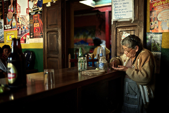 In an underworld where people go to let time go by, she works incessantly and counts the money she's made today.  ...Bar La Copa, 3a Calle Poniente #27, La Antigua, Guatemala. ..En un sub-mundo donde la gente va a pasar el tiempo, ella trabaja incesantemente y cuenta los pesos que ha hecho en la mañana de hoy. (Martin Herrera Soler)