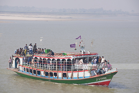 CHHOTA DHULANDI, BANGLADESH - FEBRUARY 19, 2014: Unidentified passengers cross Padma river on Daulatdia ferry boat at Chhota Dhulandi, Bangladesh. Passenger ferry boats are often overloaded in Bangladesh. (Dmitry Chulov)