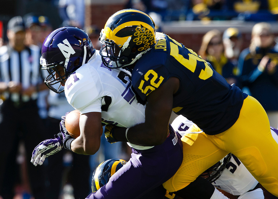 Oct 10, 2015; Ann Arbor, MI, USA; Northwestern Wildcats running back Justin Jackson (21) is tackled by Michigan Wolverines linebacker Royce Jenkins-Stone (52) in the first quarter at Michigan Stadium. Mandatory Credit: Rick Osentoski-USA TODAY Sports (Rick Osentoski/Rick Osentoski-USA TODAY Sports)