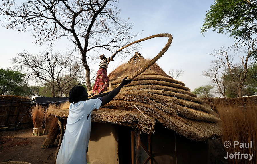 Gina Gial (below) and Mary Musiah construct a thatched roof in Agok, a town in the contested Abyei region where tens of thousands of people--including Gial and Musiah--fled in 2011 after an attack by soldiers and militias from the northern Republic of Sudan on most parts of Abyei. Although the 2005 Comprehensive Peace Agreement called for residents of Abyei--which sits on the border between Sudan and South Sudan--to hold a referendum on whether they wanted to align with the north or the newly independent South Sudan, the government in Khartoum and northern-backed Misseriya nomads, excluded from voting as they only live part of the year in Abyei, blocked the vote and attacked the majority Dinka Ngok population. The African Union has proposed a new peace plan, including a referendum to be held in October 2013, but it has been rejected by the Misseriya and Khartoum. The Catholic parish of Abyei, with support from Caritas South Sudan and other international church partners, has maintained its pastoral presence among the displaced and assisted them with food, shelter, and other relief supplies. (Paul Jeffrey)