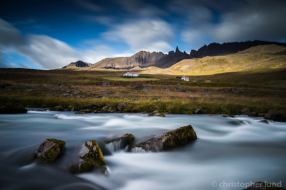 A river flowing in front of the farm Hraun in Valley Öxnadalur, North Iceland. In background rays of light hit Mount Drangafjall. The Peak Hraundrangi (1075m) was first climbed in 1956. (Christopher Lund/©2012 Christopher Lund)
