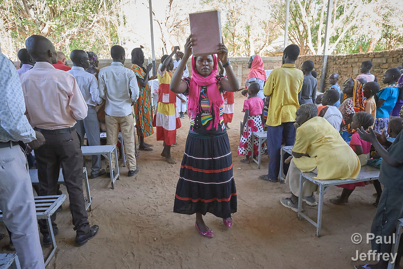 A woman carries the Bible into a Catholic Mass in Gidel, a village in the Nuba Mountains of Sudan. The area is controlled by the Sudan People's Liberation Movement-North, and frequently attacked by the military of Sudan. (Paul Jeffrey)