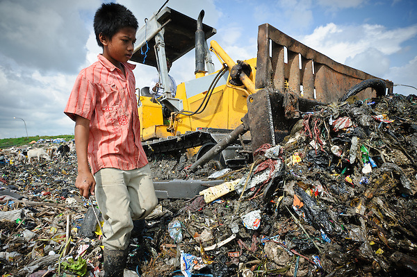 Taupik, 14, working alongside a bulldozer on the 'Trash mountain', Makassar, Sulawesi, Indonesia.  Many of the pickers follow the bulldozers as they move newly dumped waste, uncovering plastic and metal for recycling in the process. (Matthew Oldfield)