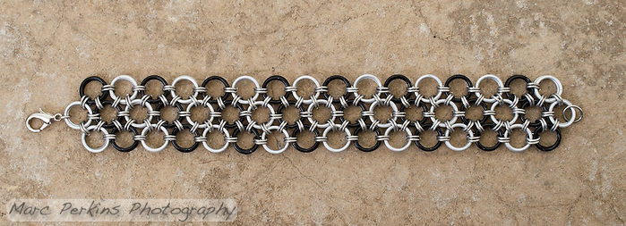 "A chainmail bracelet made by Michelle in a Japanese 12-in-2 pattern from 18 gauge 1/4"" black and white anodized aluminum rings with 20 gauge 1/8"" bright aluminum rings as connectors.  Taken on a concrete floor for a rugged background. (Marc C. Perkins)"