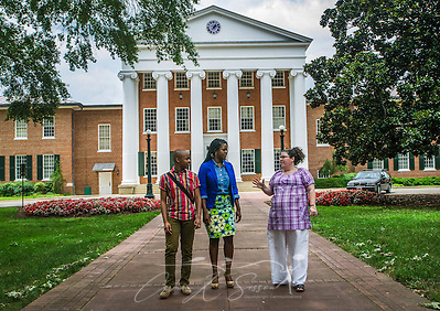 University of Mississippi students Nathaniel Weathersby and Renee Ombaba talk with Susan Glisson, executive director of the William Winter Institute for Racial Reconciliation, as they walk through The Grove on campus, July 30, 2013, in Oxford, Miss. Ombaba and Glisson organized a candlelight unity walk last fall after a racially-charged skirmish broke out in front of the Lyceum (pictured behind them) following the re-election of President Barack Obama. The Lyceum was also the site of violence in October 1962, when riots broke out after James Meredith enrolled as the first black student on campus. (Photo by Carmen K. Sisson) (Carmen K. Sisson/Cloudybright)