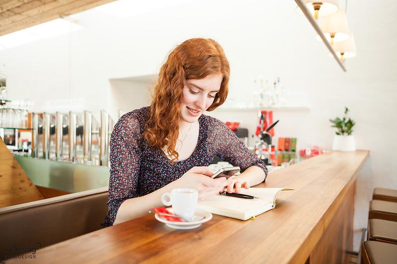 Creative Workplace, junge Frau, kreativ, Kaffeepause, Arbeiten außerhalb des Büros, Mobiltelefon, Restaurant, Österreich, Horn (dieter schewig)