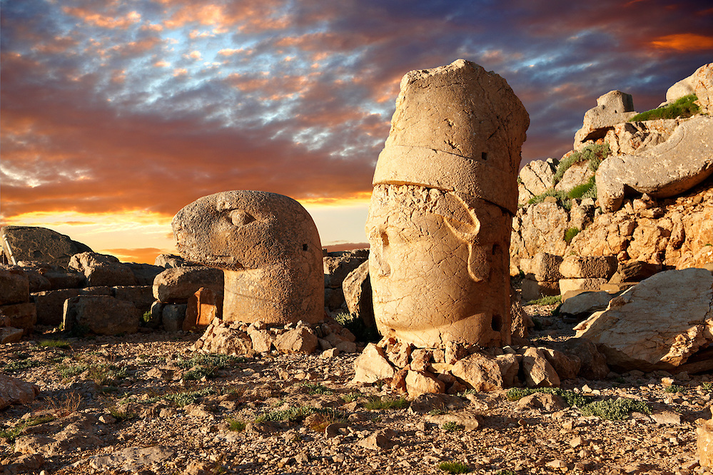 Pictures of the statues of around the tomb of Commagene King Antochus 1 on the top of Mount Nemrut, Turkey. Stock photos & Photo art prints. In 62 BC, King Antiochus I Theos of Commagene built on the mountain top a tomb-sanctuary flanked by huge statues (8–9 m/26–30 ft high) of himself, two lions, two eagles and various Greek, Armenian, and Iranian gods. The photos show the broken statues on the  2,134m (7,001ft)  mountain. 6 (Paul E Williams)