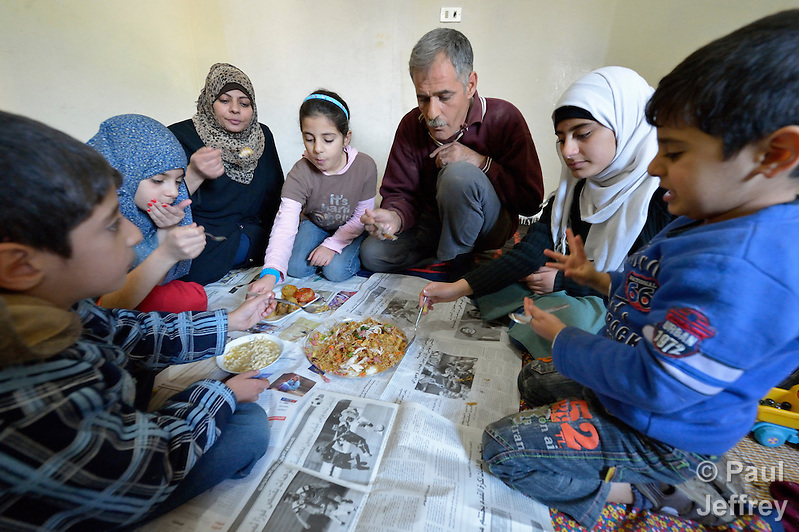 Souad Kasem Issa and her husband Ziad Hasan Noaman, along with five of their six children, share a meal in the apartment where they live in Amman, Jordan. The family of eight fled the city of Homs, Syria, as fighting there worsened in 2012. Their home in Syria has since been destroyed by bombing, and they are struggling to survive in Jordan's capital city. They are receiving some assistance from International Orthodox Christian Charities, is a member of the ACT Alliance. (Paul Jeffrey)