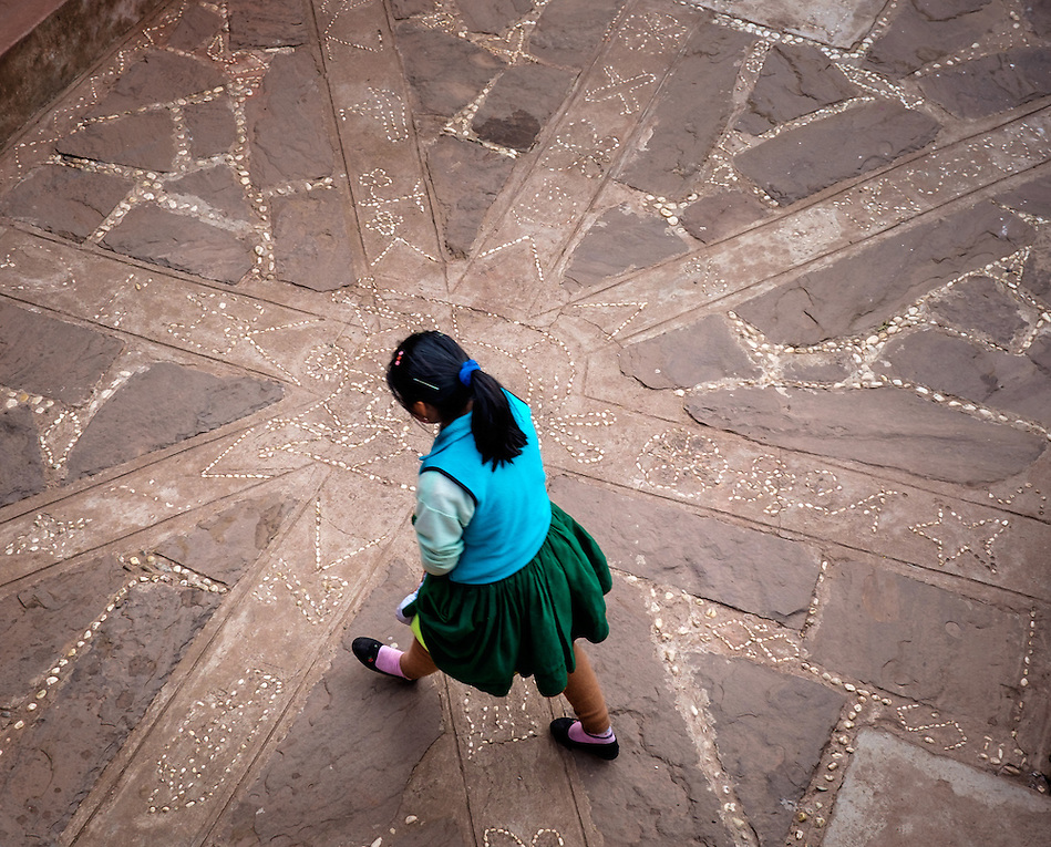 TAQUILE, PERU - CIRCA OCTOBER 2015: Young woman walking in a typical patio in the Island of Taquile in Lake Titicaca. (Daniel Korzeniewski)