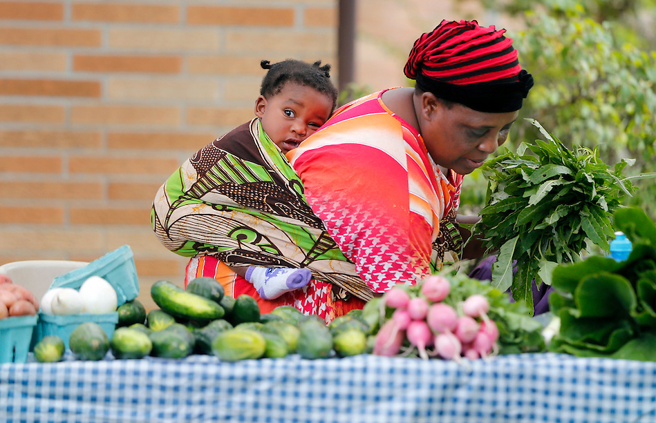 Burundian immigrant Beuline Bucumi assembles her produce as her granddaughter, Sadia, 1, rests in a sling on her back during the Global Greens Farmers Market at Lutheran Services in Iowa on Saturday, August 23, 2014 in Des Moines.  The market, launched in June, features fruits and vegetables grown by displaced farmers who have resettled in Iowa. (Christopher Gannon/The Register)