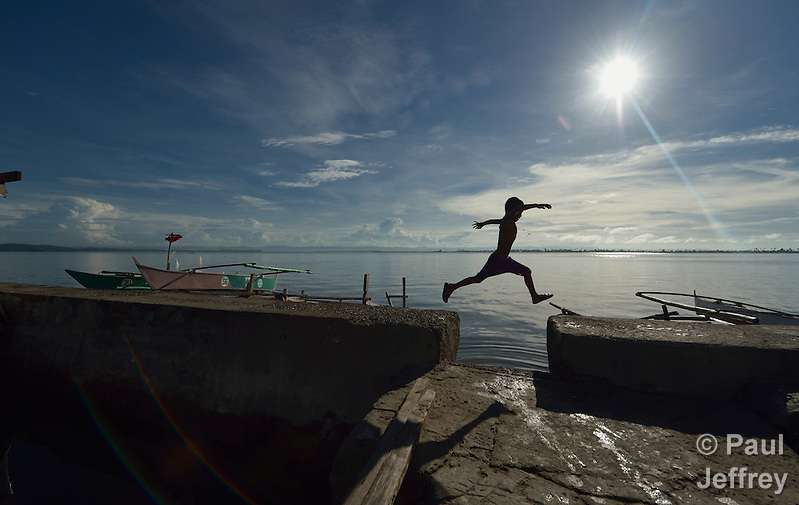 Seven-year old Mark Dave Mortiga, nicknamed Pipoy, jumps a gap in a walkway along the sea in Tacloban, a city in the Philippines that was hard hit by Typhoon Haiyan in November 2013. Known locally as Typhoon Yolanda, the storm surge buried this area with water, destroying the neighborhood. Despite a government prohibition on rebuilding within 40 meters of the shoreline, residents say they have nowhere else to go and have constructed new dwellings over the water. The ACT Alliance has accompanied survivors in this neighborhood and other areas impacted by the typhoon as they rebuild their communities and livelihoods. (Paul Jeffrey)