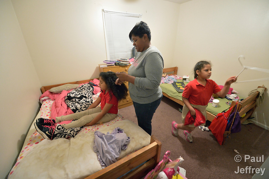 Sonnet Pichardo helps her daughters Rhinaye (left) and Savannah get ready for school in their bedroom early in the morning in their home in Columbus, Georgia. Pichardo successfully participated in Circles of Hope, a program to end poverty and build financial independence sponsored by the Open Door Community House in Columbus. (Paul Jeffrey)