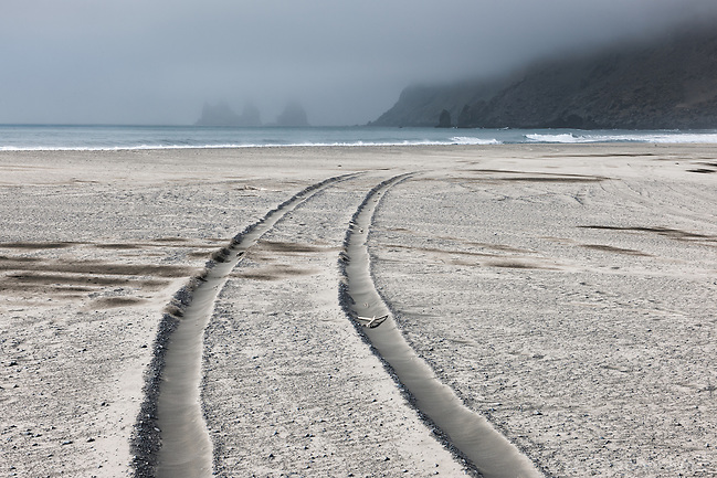 Ash from Volcano Eyjafjallajökull on the usually black sand beach of Vík, South Iceland. Tire tracks in the sand. Reynisdrangar Sea Stacks in background, ashcloud above. (Christopher Lund/©2010 Christopher Lund)