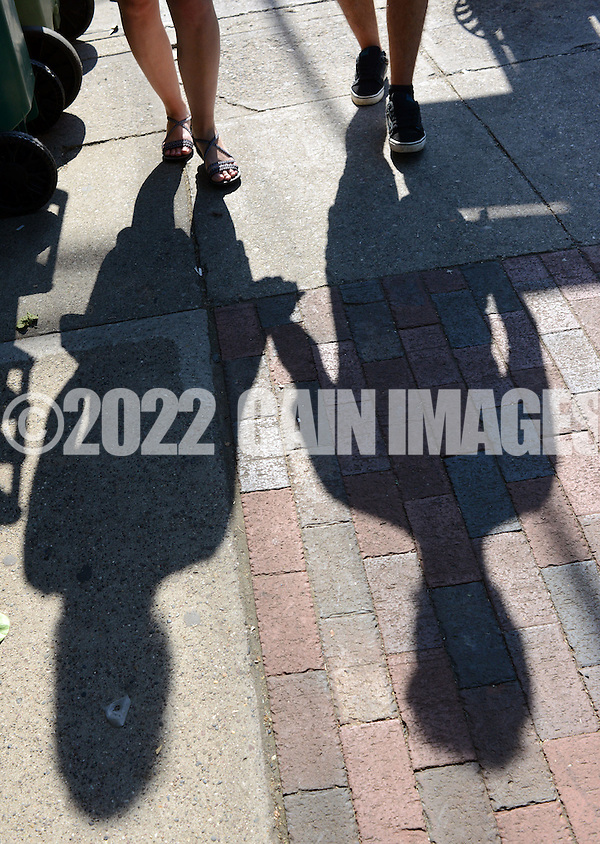 NEW HOPE, PA - JUNE 02: Debbie Morrison, 31, of Seargentsville, New Jersey and Miguel Santana, 23, of Spain walk together as their shadows cast as they hold hands on a warm afternoon June 2, 2014 in New Hope, Pennsylvania.  The temperature reached 82 degrees in New Hope and is expected to remain in the mid-80's for the next few days. (Photo by William Thomas Cain/Cain Images) (William Thomas Cain)
