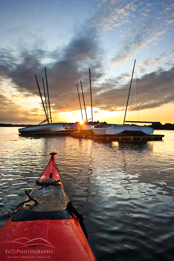 The bow of a kayak and moored sailboats at sunrise in Portsmouth Harbor in Portsmouth, New Hampshire. (Jerry and Marcy Monkman)