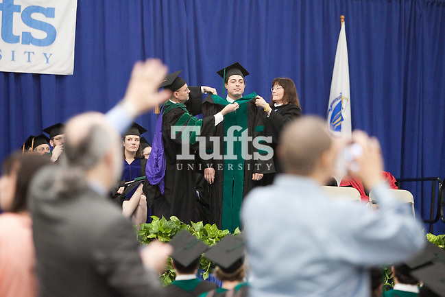 05/22/2011- Medford, Mass. - A newly graduated physician receives his hood as family members wave to other graduates during commencement for the Tufts University School of Medicine on May 22, 2011. (Kelvin Ma/Tufts University) (Kelvin Ma/Tufts University)