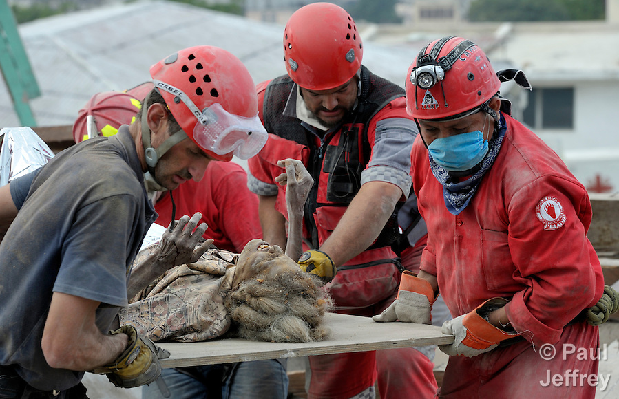Ena Zizi is pulled alive on January 19 from the rubble of Haiti's devastating earthquake, one week after the city was reduced to ruins in a matter of seconds. The 70-year old woman was rescued from the collapsed home of the parish priest at Port-au-Prince's Roman Cathedral Cathedral of Our Lady of the Assumption by members of a Mexican search and rescue team, several of whom were in tears as they pulled the woman free from tons of rubble. She suffered from dehydration, a dislocated hip and a fractured leg, and was taken by helicopter to the U.S.S. Bataan for treatment. She told an interviewer she stayed alive by talking with God. (Paul Jeffrey)