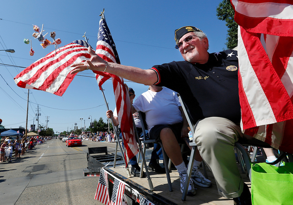 David Lamb of Johnston, a Vietnam War veteran, tosses candy to children during an Independence Day parade Friday morning in Urbandale. (Christopher Gannon/The Register)